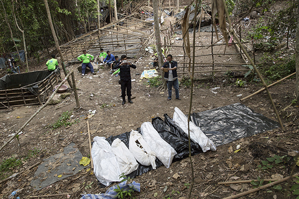 A policeman and a rescue worker take pictures of bodies retrieved from a mass grave at an abandoned camp  in Thailand's southern Songkhla province